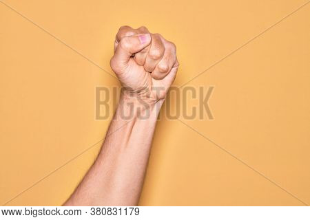 Hand of caucasian young man showing fingers over isolated yellow background doing protest and revolution gesture, fist expressing force and power
