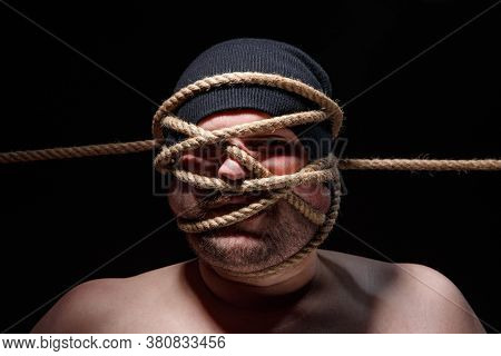 Photo Of Binded Fat Man In Cap With Rope On Face