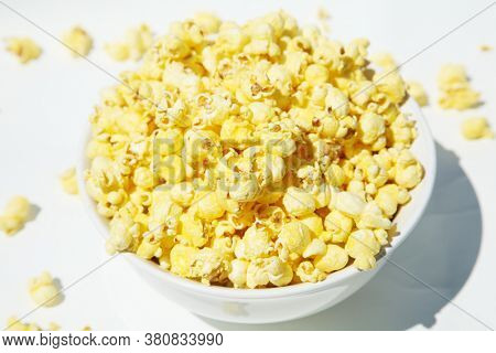 Popcorn in a white bowl isolated on white. Bowl of buttered popcorn on a white background.