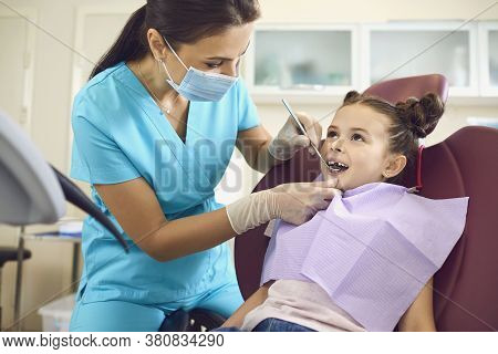Little Girl At A Pediatric Dentist With Mask And Gloves Service Child Tooth Care In A Dental Dentist