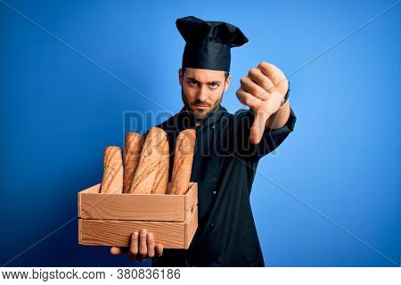 Young cooker man with beard wearing uniform holding box with bread over blue background with angry face, negative sign showing dislike with thumbs down, rejection concept