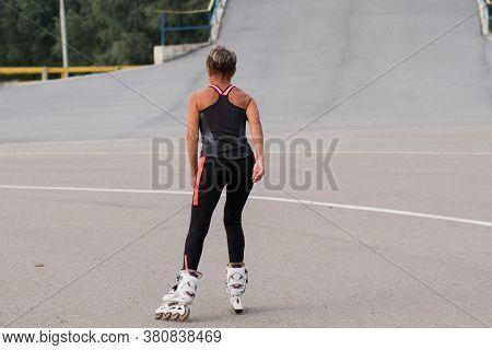 Active Seniors Woman Roller-skating Rear View At The Stadion