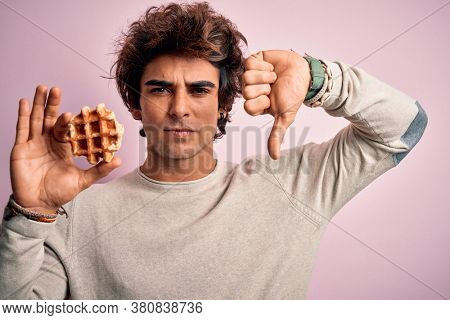 Young handsome man holding sweet waffle standing over isolated pink background with angry face, negative sign showing dislike with thumbs down, rejection concept