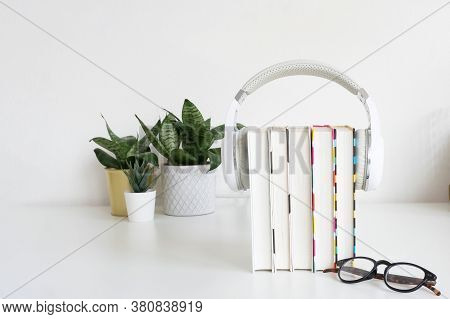 White Headphones On A Stack Of 5 Book, Glasses And Indoor Flowers On The Table Against The Backgroun