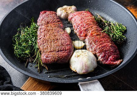 Cooking Denver Steak On Grill Frying Pan With Garlic And Herbs Just From Fire Side View