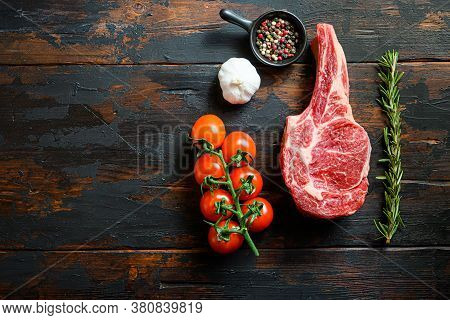 Raw Uncooked Black Angus Bone In Steak In Rustic Style On Wooden Table Background. With Tomato Garli