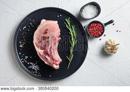 Raw Pork Loin Chops  In A Black Round Plate On A White Stone Background With Rosemary Garlic Pepperc
