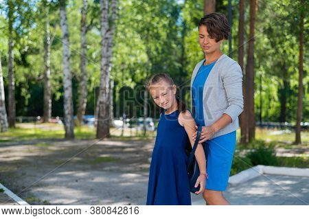 A Caring Mother Helps Her Child Put On A Backpack. Caucasian Woman Preparing Her Daughter For School