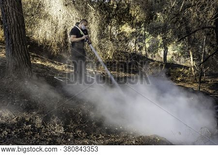 Jerusalem, Israel - August 4th, 2020: Two Israeli Firemen Putting An End To A Forest Fire Near Jerus