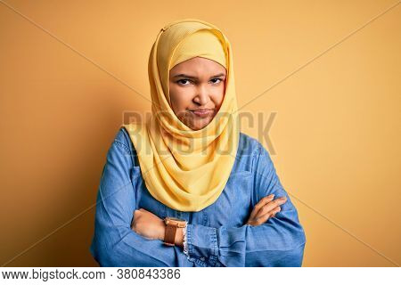 Young beautiful woman with curly hair wearing arab traditional hijab over yellow background skeptic and nervous, disapproving expression on face with crossed arms. Negative person.