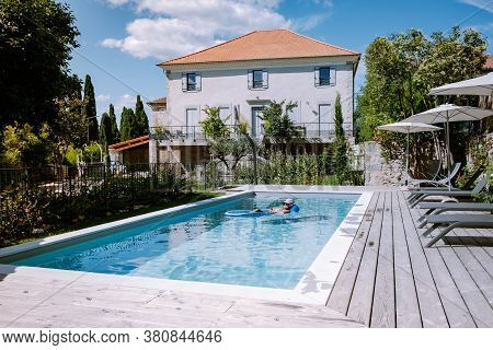 French Vacation Home With Wooden Deck And Swimming Pool In The Ardeche France. Woman Relaxing By The