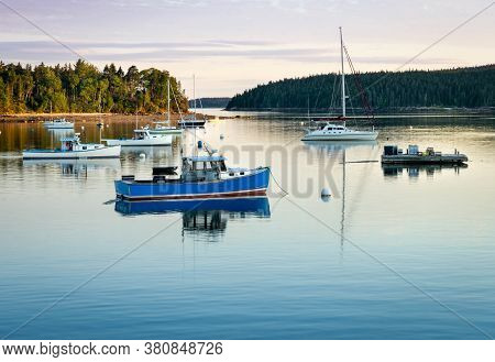 Several Boats Moored In A Small Cove In Pretty Marsh In Maine On A Beautiful Evening With A Sunset.