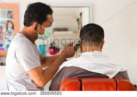 Bangkok, Thailand - September 2, 2020 : Asian Confident Men Hairdresser Is Using Hair Clipper To Cut