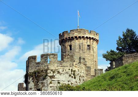 Tower And Battlements Of A Medieval English Castle On A Grassy Mound Against Blue Sky