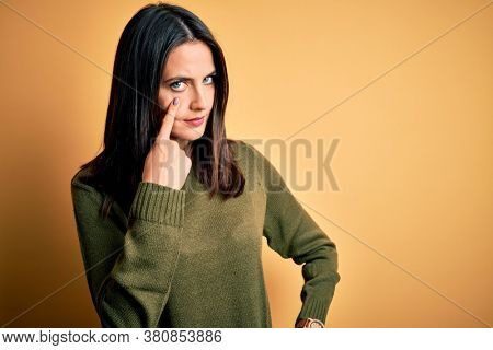 Young brunette woman with blue eyes wearing green casual sweater over yellow background Pointing to the eye watching you gesture, suspicious expression