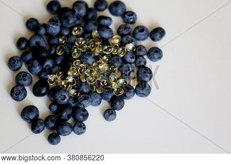 Heap Of Fresh Blueberry And Small Capsules Of Vitamin D As Food Supplements Close Up Taken On The Wh