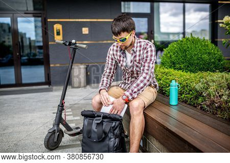 Handsome Hipster Style Bearded Man Works Online Freelancer, Pulls Out Laptop With Backpack And Elect