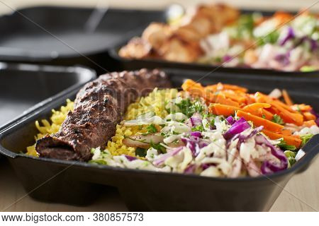 greek beef souvlaki take out container with rice and pickled vegetables