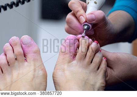 Beautician Polishing Nails With A Device, Pedicure.