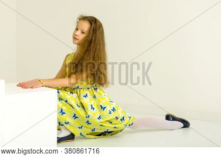 Beautiful Girl Wearing Yellow Dress And Blue Shoes Sitting On Twine On White Floor In The Room, Side