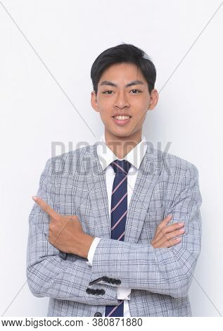 young handsome businessman  wearing in striped gray suit ,tie with white shirt and finger to the side