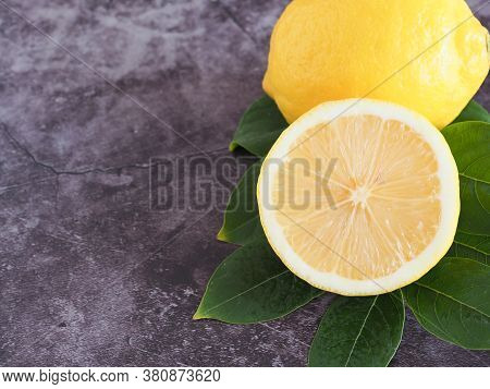 Close Up Half Lemon With Green Leaves On Dark Grey Background With Copy Space. High Vitamin C, Which