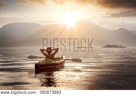 Woman Relaxing On Her Kayak During A Colorful Summer Sunset. Taken In Howe Sound, North Of Vancouver