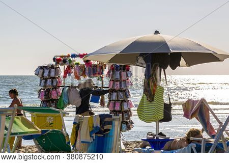 Castel Volturno, Italy - August 18, 2019: Beach Seller With His Goods On The Beach Of Castel Volturn