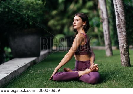 Woman Practicing Yoga-asanas Outdoors. Young Attractive Slim Fitness Girl In Bodysuit Relaxing And D
