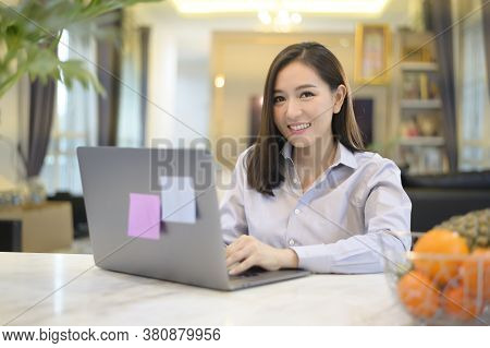 A Beautiful Asian Business Woman Is Working With Her Computer At Home , Telecommunication , Social D