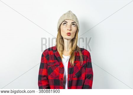 Young Woman With A Pensive Face Dreams Of Something In A Hat, A Red Shirt And A White T-shirt On A W