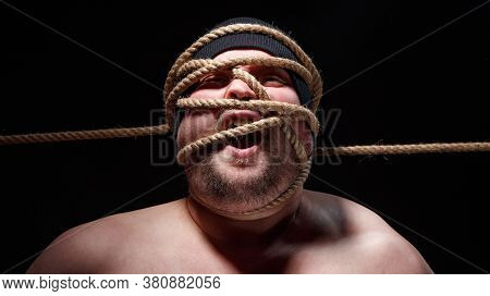Portrait Of Binded Screaming Fat Man In Cap With Rope On Face