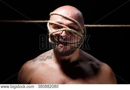 Photo Of Binded Bald Man With Rope On Face