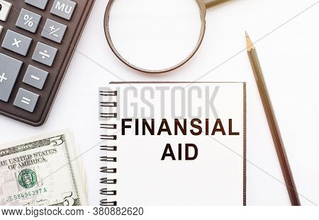 Financial Aid Text Written On A Notebook With Pencil, Calculator, Magnifier And Dollars