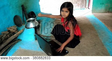 District Katni, India - August 14, 2019: An Indian Village Little Poor Girl Operating Laptop During