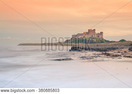 Bamburgh Castle In Northumberland At Sunset - View From The Beach