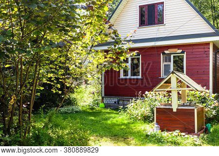View Of Wooden Summerhouse And Well On Backyard In Russia On Sunny Summer Day