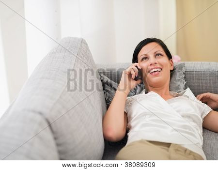 Smiling Young Woman Laying On Sofa And Speaking Mobile Phone