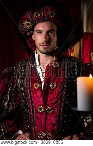 Portrait Of Handsome King With Beard Dressed In Costume Looking At Camera With Candle In Foreground