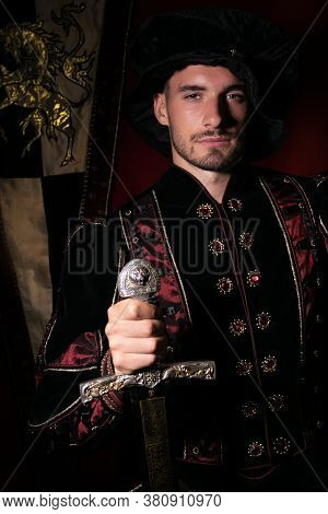 Portrait Of Handsome King With Beard Dressed In Costume, Holding Sword And Looking At Camera
