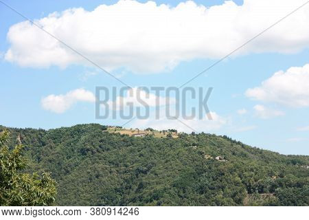 Between The Green Tuscan Hills And The Rural Villages In The Rustic Countryside And Sky