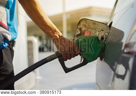 Refuel Cars At The Fuel Pump. The Driver Hands, Refuel And Pump The Car's Gasoline With Fuel At The