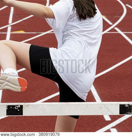 A Young Girl Is At Running Summer Camp Learning How To Run Over The Hurdles.