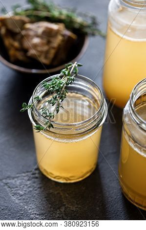 Glass Jar With Yellow Fresh Bone Broth On Dark Gray Background. Healthy Low-calories Food Is Rich In