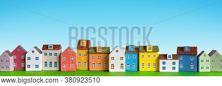 Colorful Miniature Houses Arranged In A Row On Blue Background. Urban City Background Banner. Copy S