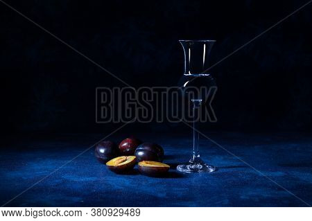 Plum Brandy Slivovice In Shot Glass With Fresh Ripe Plums On Blue Table With Dark Background.