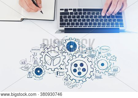 Top View Of Businessman Using Laptop On Table With Gears Sketch Drawn On It. Concept Of Teamwork. To