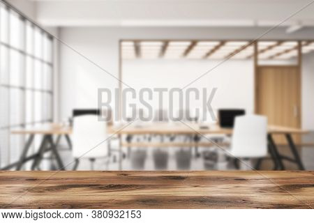 Wooden Table For Your Product In Blurry Open Space Office With White Walls, Concrete Floor, Wooden C