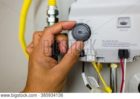 Close Up Shot Of A Plumber Male Hand Adjusting A Modern Hot Water Heater Control Thermostat. Great I