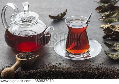 Glass Turkish Brewed Black Tea And Glass Teapot With Dry Black Tea In Burlap Sack On Black Rustic Ta